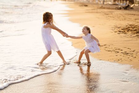 girl children in white dresses playing on the beach. older sister pulls the younger into the water. a fun filled family vacation.