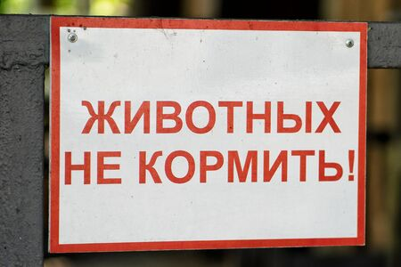 A sign at the zoo with the inscription in Russian - do not feed the animals. Harmful food for animals, penalties for the visitors. Stock Photo