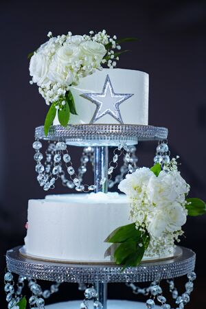 a large white cake decorated with beads and flowers. wedding traditions.