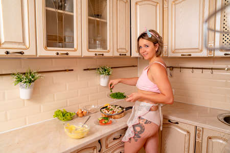 housewife with a tattoo in panties adds to the dish with fresh chopped parsley. healthy, organic food. Stock fotó