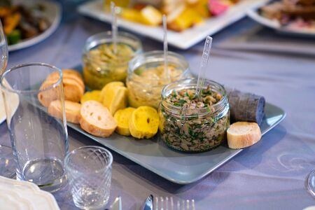 snacks, pickles in small jars and bread on the holiday table. catering and food delivery.