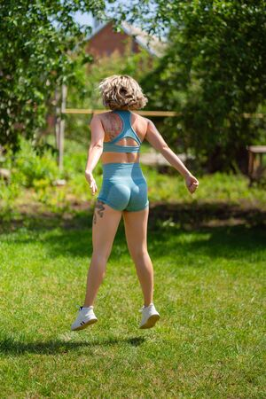 rear view. squat and jumping exercises. blonde girl with tattoos plays sports in the garden. recovery and fitness after childbirth.