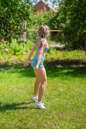 side view. squat and jumping exercises. blonde girl with tattoos plays sports in the garden. recovery and fitness after childbirth.