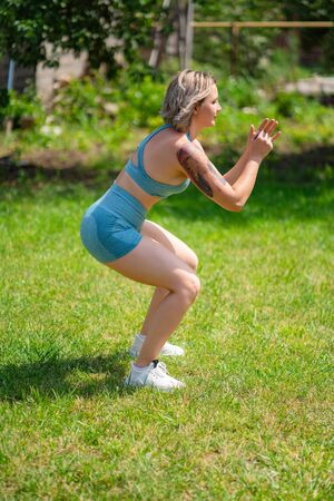 side view. squat exercises. blonde girl with tattoos plays sports in the garden. recovery and fitness after childbirth.