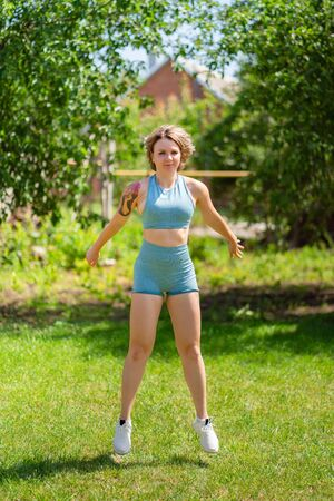 squat and jumping exercises. blonde girl with tattoos plays sports in the garden. recovery and fitness after childbirth. Foto de archivo