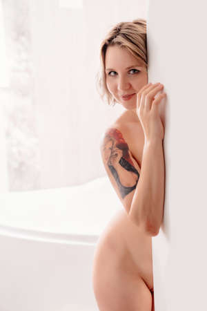 Nude sexy girl with a tattoo of his face on her shoulder standing at the door to the bathroom.