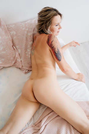 sexy blonde girl with a tattoo. Nude woman lying on the bed in the small bedroom. rear view. Stockfoto