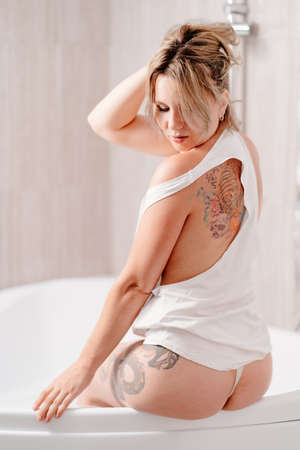 rear view. sexy girl with tattoos in a white tank top sitting on the edge of the tub. skin care at home.