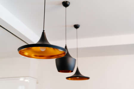 copper chandelier painted black on the ceiling. the lighting in the interior. Standard-Bild