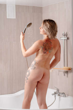rear view. Nude sexy girl with tattoos takes a shower standing in the tub. hygiene and skin care at home.