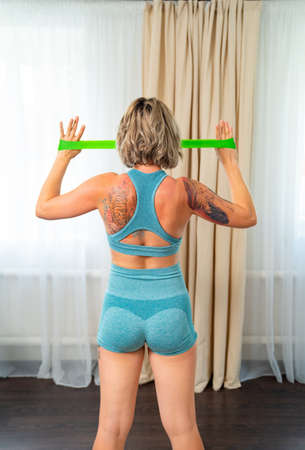 rear view. girl with tattoos are engaged fitness with rubber bands in home. sports exercises.