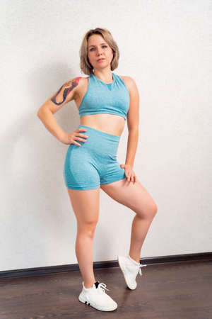 girl with tattoo in sportswear is engaged in home fitness and posing against the wall. online sports. recovery after childbirth.