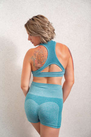 rear view. girl with tattoo in sportswear is engaged in home fitness and posing against the wall. online sports. recovery after childbirth.