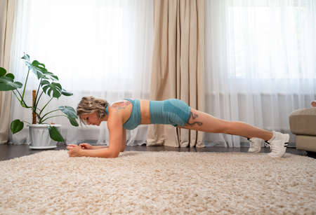 girl with tattoos plays sports at home, exercise plank handstand. online fitness. recovery after childbirth. Фото со стока