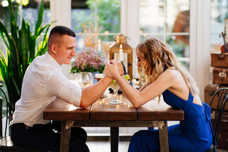 two cheerful lovers out who's in charge and fight on hand at a romantic dinner. arm wrestling