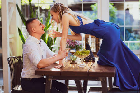 romantic dinner for a couple in love. girl with a glass of wine stands on the table to kiss her boyfriend.