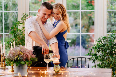 love happy couple on a romantic dinner with glasses. the guy pours the champagne and make an offer hands and hearts.