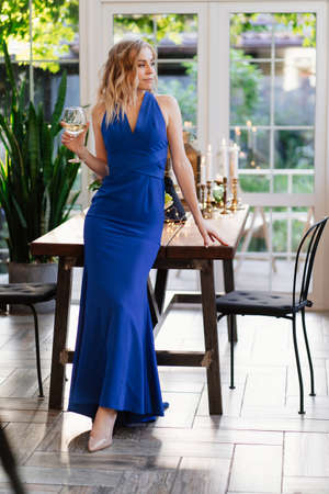 beautiful blonde girl with long hair in a blue dress standing with a glass of wine. a romantic dinner. 免版税图像