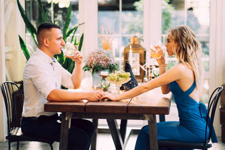 romantic dinner for a couple in love in a beautiful country house. lovers drink wine from glasses.