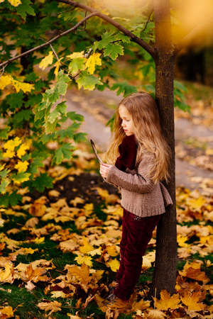 little dreamy girl is standing under the tree in autumn Park with a bird feather in hand. the concept of reverie and inspiration.