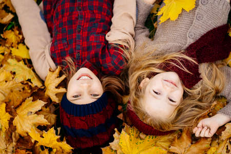 two little girls in the hat lying on the ground on yellow maple leaves in autumn Park