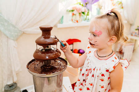 little girl with face paint eating chocolate from the chocolate fountain at a children's party Foto de archivo