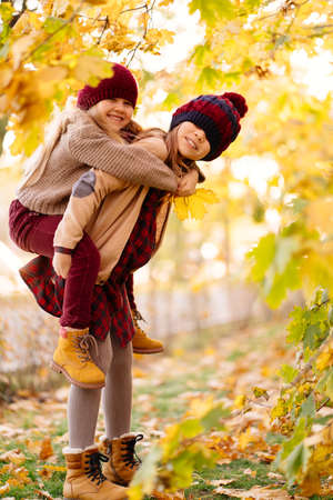 two girls in hats are playing and having fun in autumn park under yellow maples. the older sister rolls a younger. the concept of friendship.