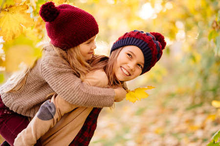 two girls in hats are playing and having fun in autumn park under yellow maples. the older sister rolls  a younger. the concept of friendship. 版權商用圖片