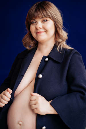 without retouching. Topless, beautiful pregnant woman with overweight in a blue jacket. obesity, cellulite and stretch marks. blue wall