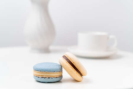 macarons on background tea Cup and a vase on a white table. table setting for tea.