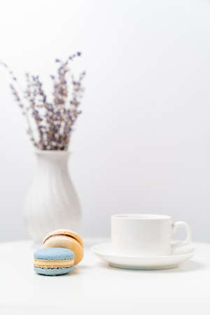 macarons on background tea Cup and a vase with lavender on a white table. table setting for tea.
