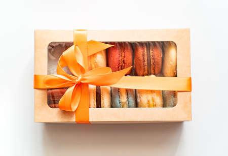 gift box with orange ribbon and colorful macaron inside on a white background. Zdjęcie Seryjne
