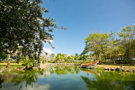 a pond with a colorful boat surrounded by gardens and trees in a tropical country. vacation in an exotic place. Stock fotó - 152478170
