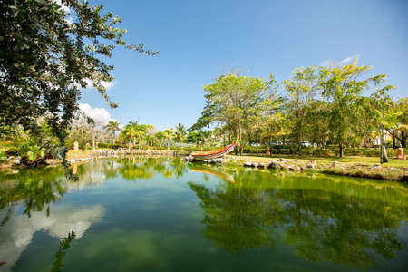 a pond with a colorful boat surrounded by gardens and trees in a tropical country. vacation in an exotic place.