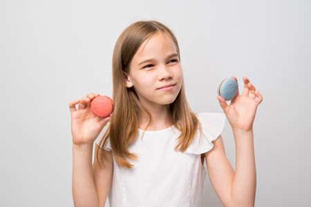 teenager girl in a white dress holding a macarons made from natural ingredients. the concept of healthy and natural desserts.