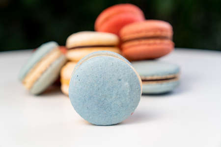 multicolored macarons from natural ingredients and colors on a white table.
