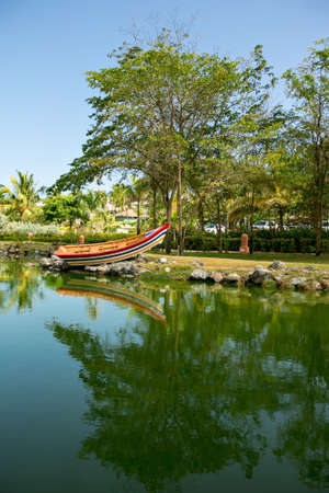 a pond with a colorful boat surrounded by gardens and trees in a tropical country. vacation in an exotic place. Stock fotó - 152478025
