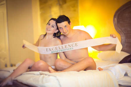 loving couple sitting on the bed with ribbon - excellence honeymooners. the journey after the wedding.