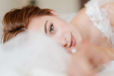 beautiful girl with natural makeup, well-groomed and glowing skin lies in bed.