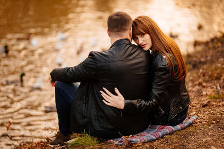couple in love, a man and a woman sitting on the Bank of the river in an autumn park. romantic walk. Foto de archivo