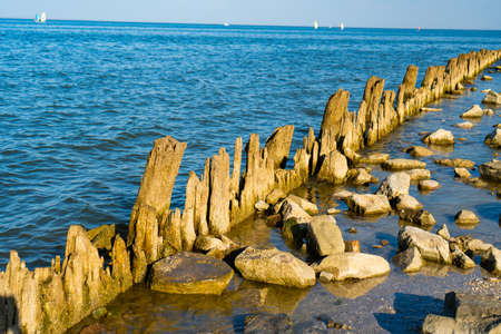 old broken wooden posts covered in seaweed and rocks in the sea. the place is unsuitable for swimming.