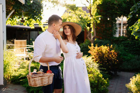 a couple waiting for a baby walks in the garden with a picnic basket. family walks in the Park. happy pregnancy.
