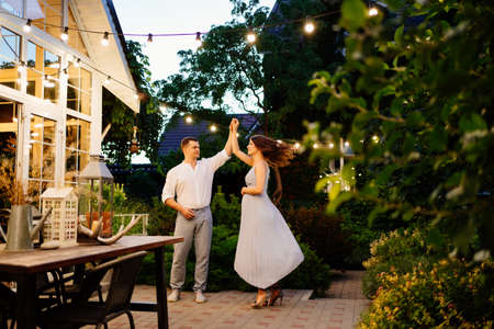 a pregnant woman and a man in smart clothes is dancing in the evening in garden in a country house by the fireplace. romantic relationships in the family.