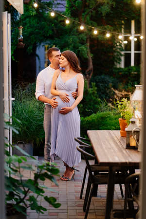 a pregnant woman and a man in smart clothes in the evening in garden in a country house by the fireplace. romantic relationships in the family. Stock fotó