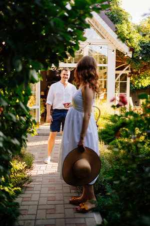 a beautiful pregnant woman in a white dress with a hat and a picnic basket walks in the Park with her husband. walking in the fresh air. happy pregnancy.
