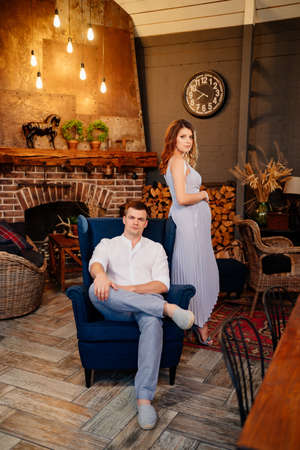 a pregnant woman and a man in smart clothes in the evening in a country house by the fireplace sit on a chair. romantic relationships in the family.