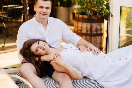 portrait of a beautiful pregnant woman in a white dress lying on the lap of a man and holding her husband hand during a picnic. happy romantic family relationships. Stock fotó