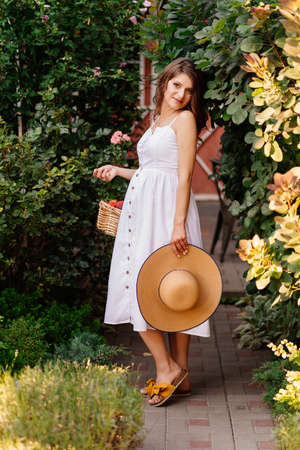 a beautiful pregnant woman in a white dress with a hat with a picnic basket walks in the Park. walking in the fresh air. happy pregnancy.