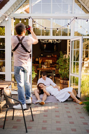 a professional photographer takes a picture of a couple expecting a baby in the backyard garden. it is a tradition to take photos as a souvenir. pregnancy photo shoot. backstage