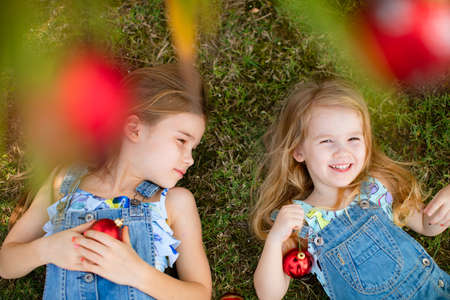 little girls with long hair in denim overalls lie on the grass under a palm tree with red Christmas toys. happy carefree childhood. new year in the tropics. Stock fotó